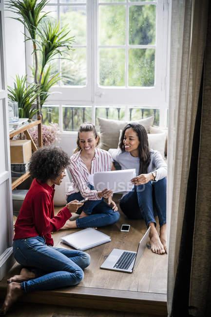 Tre donne con laptop, telefono cellulare e documenti seduti a casa — Foto stock