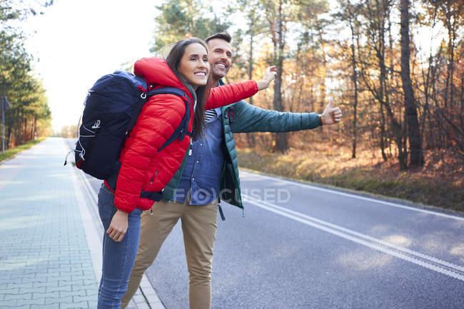 Щаслива пара під час подорожі автостопом у лісі. — стокове фото