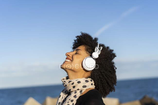 Mulher sorridente ouvindo música com fones de ouvido brancos perto do mar — Fotografia de Stock