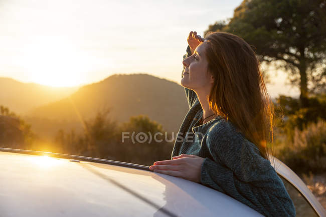 Young woman on a road trip, taking a break, shielding eyes — Stock Photo