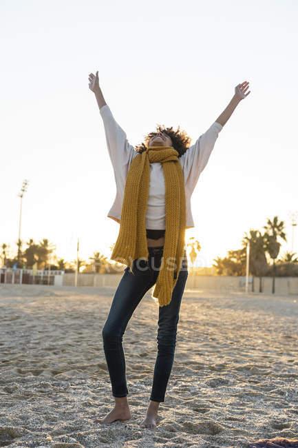 Femme heureuse s'amuser sur la plage au coucher du soleil — Photo de stock