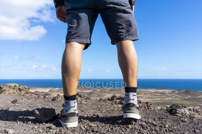 Spain, Canaray Islands, Fuerteventura, legs of a man standing at the coast — Stock Photo