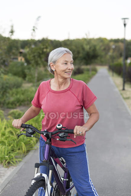 Senior woman with bicycle on bicycle lane — Stock Photo