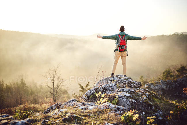 Man on a hiking trip in the mountains standing on rock enjoying the view — Stock Photo