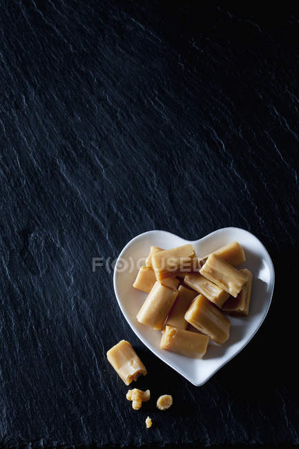 Cream toffees on a heart-shaped plate — Foto stock