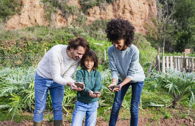 Семья, держащая землю в руках — стоковое фото