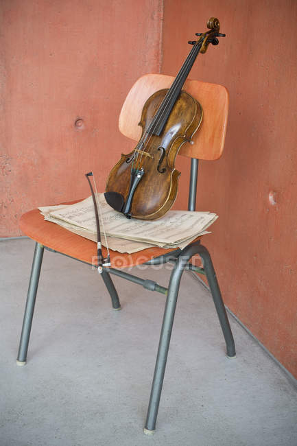 Violon, archet et partitions sur chaise en bois — Photo de stock