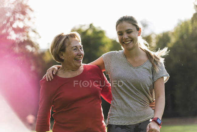 Granddaughter and grandmother having fun, jogging together in the park — Foto stock