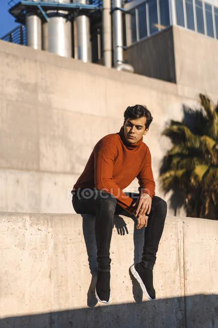 Retrato de un joven de moda con jersey de cuello alto sentado en una pared a la luz del sol - foto de stock