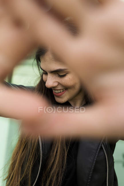 Happy young woman raising her hands — Stock Photo