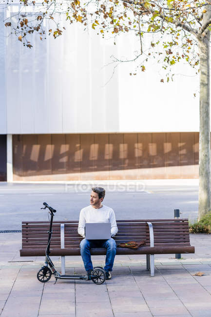 Uomo d'affari casual con kick scooter, seduto su una panchina, che lavora rilassato in città — Foto stock