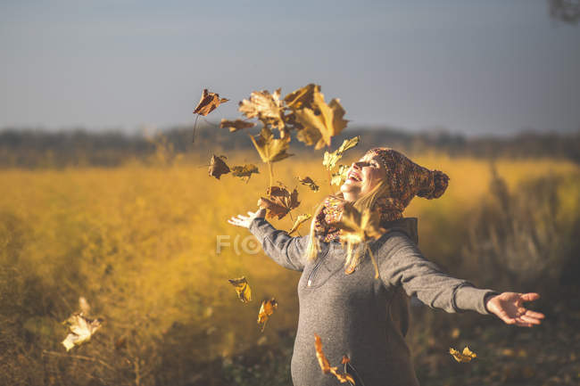Happy pregnant woman playing with autumn leaves in nature — Stock Photo