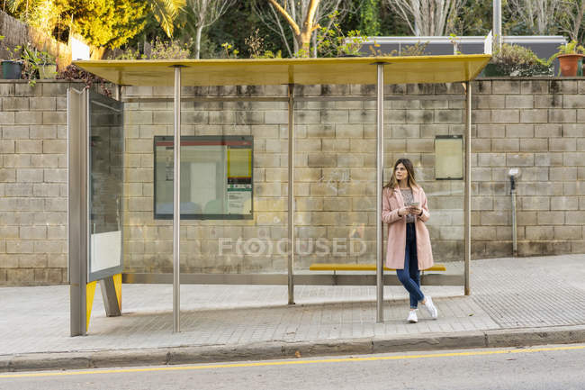 Young woman with cell phone waiting at bus stop — Stock Photo