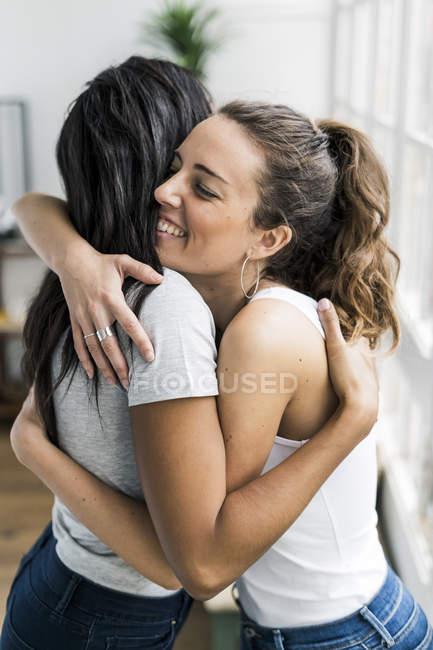 Дві щасливі дівчини, які обіймаються вдома. — стокове фото