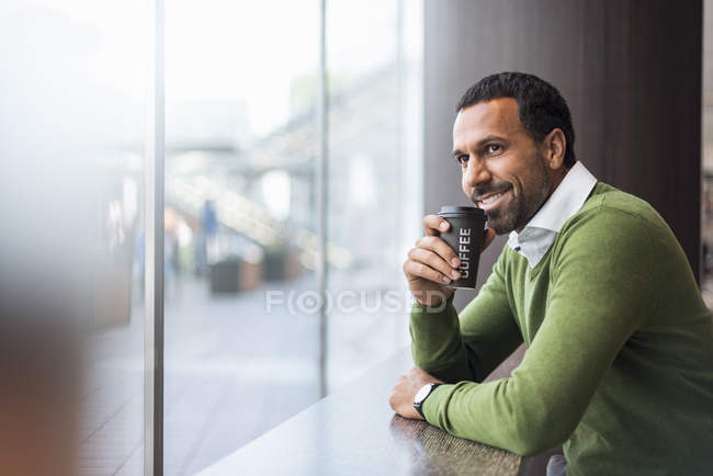 Businessman with coffee to go in a cafe — Stock Photo