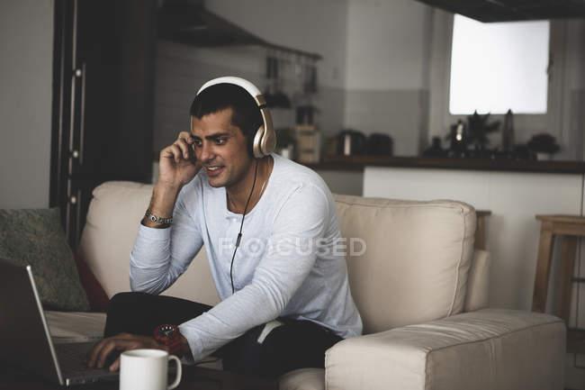 Sonriente joven sentado en el sofá en casa con auriculares y el uso de la computadora portátil - foto de stock