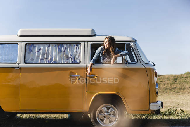 Pretty woman on a road trip with her camper, looking out of car window — Foto stock