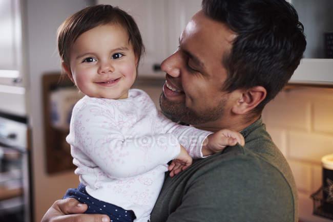 Portrait de père souriant tenant bébé fille à la maison — Photo de stock