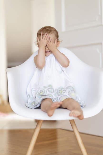 Menina criança sentada em uma cadeira cobrindo os olhos com as mãos — Fotografia de Stock