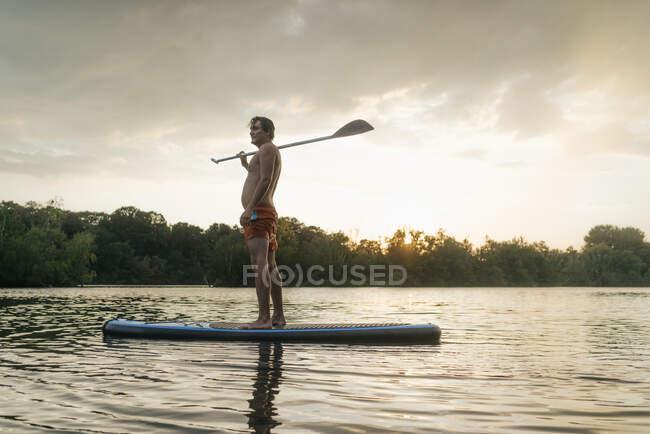 Hombre de pie a bordo de SUP en un lago al atardecer - foto de stock