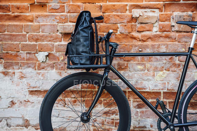 Backpack in cargo cage of acustomised commuter fixie bike at brick wall — Stock Photo