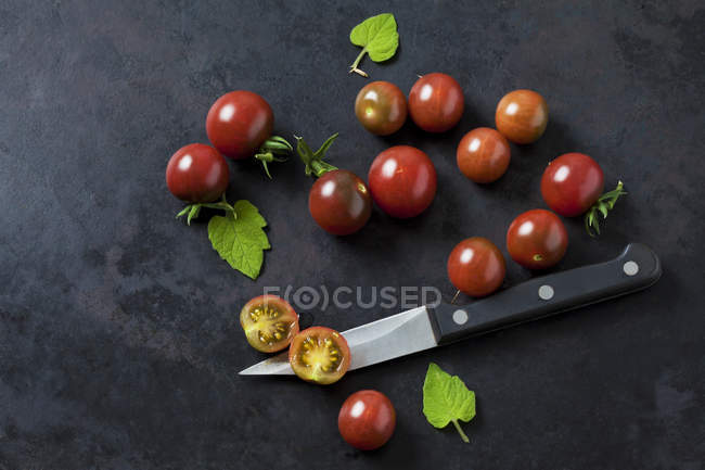 Whole and sliced risp tomatoes 'Black Cherry', leaves and kitchen knife on dark ground — Stock Photo