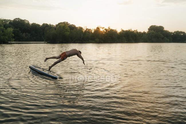 Людина стрибає з позашляховика на озері на заході сонця. — стокове фото