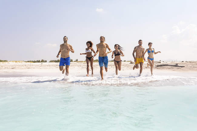 Group of friends having fun on the beach, running into the water — Stock Photo