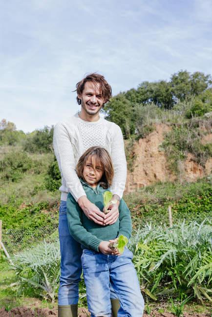 Père et fils tenant des plantules de laitue dans un potager — Photo de stock