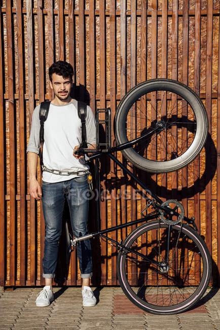 Porträt eines jungen Mannes mit Rucksack mit Pendler-Fixie-Fahrrad — Stockfoto