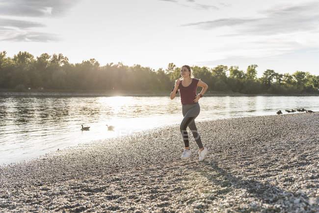 Молодая женщина бегает по реке — стоковое фото