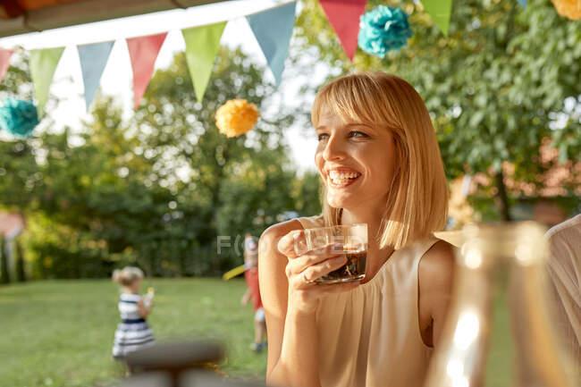 Щаслива жінка п'є каву на городі. — стокове фото