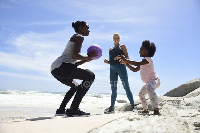 Мать с дочерью и другом занимаются с мячом на пляже — стоковое фото