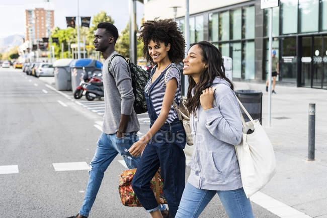 Tre amici che passeggiano per la città — Foto stock