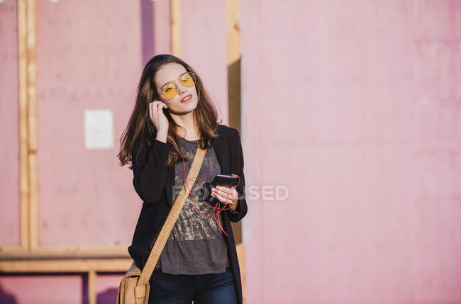 Young woman with cell phone and earphones wearing coloured sunglasses — Stock Photo