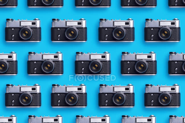 Photo cameras organized in a row over blue background — Stock Photo