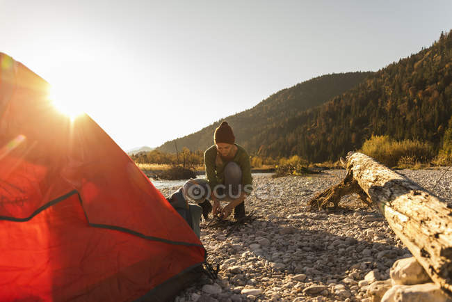Mature woman camping at riverside, collecting wood for campfire — Stock Photo