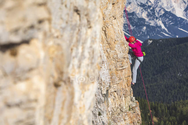 Italy, Cortina d'Ampezzo, woman climbing in the Dolomites mountains — Stock Photo