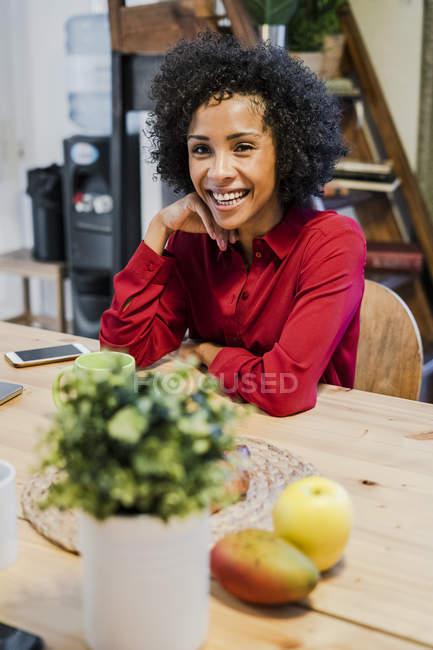 Portrait de femme heureuse assise à table — Photo de stock