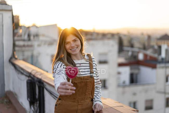 Ritratto di sorridente giovane donna che regala lecca rossa sulla terrazza sul tetto al tramonto — Foto stock