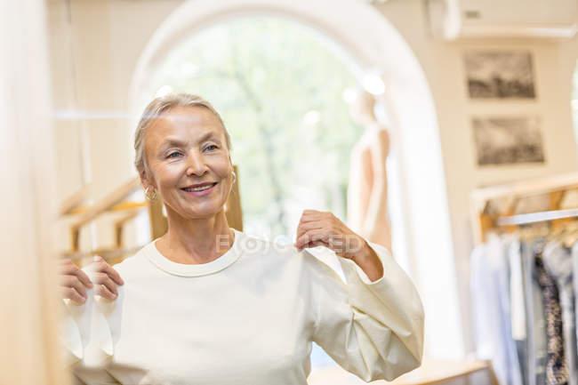 Улыбающаяся пожилая женщина примеряет пуловер в бутике — стоковое фото