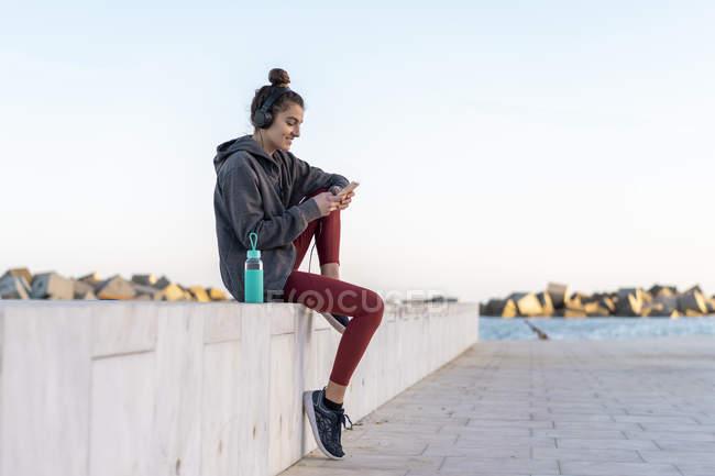 Jeune femme sportive avec écouteurs pendant l'entraînement, en utilisant un smartphone — Photo de stock