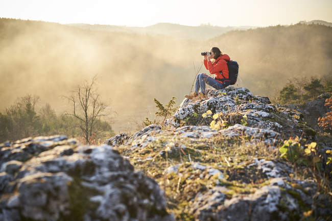 Woman on a hiking trip in the mountains sitting on rock looking through binoculars — Stock Photo