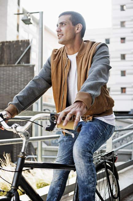 Giovane in bicicletta in città — Foto stock