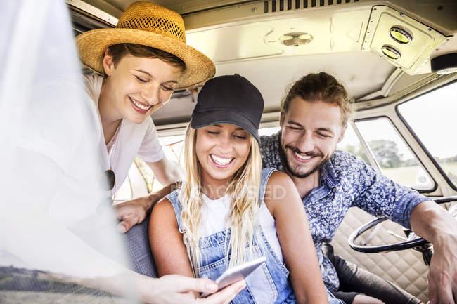 Happy friends inside van looking at smartphone — Stock Photo