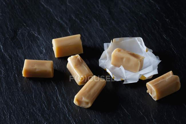 Toffees de crème et papier d'emballage sur ardoise noire — Photo de stock