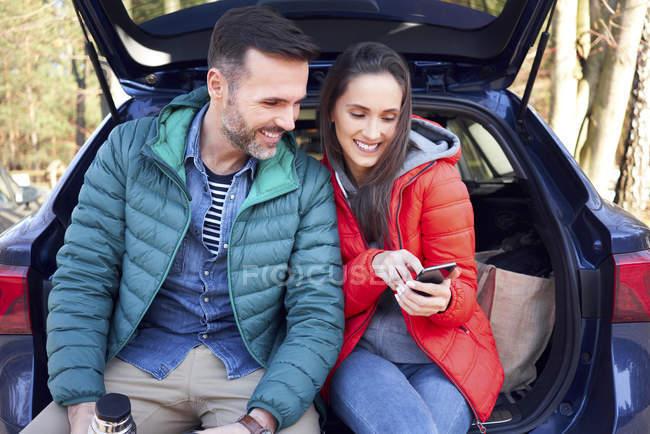 Пара, использующая смартфон, сидя в багажнике автомобиля во время поездки — стоковое фото