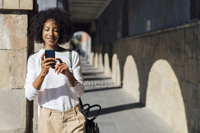 Young casual businesswoman using smartpone in the city — Stock Photo