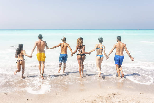 Group of friends at the beach, running into the sea, holding hands — Stock Photo