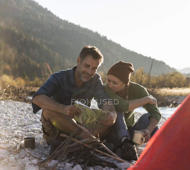 Mature couple camping at riverside, looking on map — стоковое фото